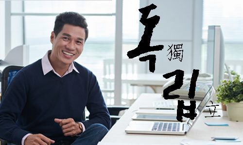 Positive Asian man pointing finger aside. Young guy recommending something. Advertisement concept. Isolated front view on white background.